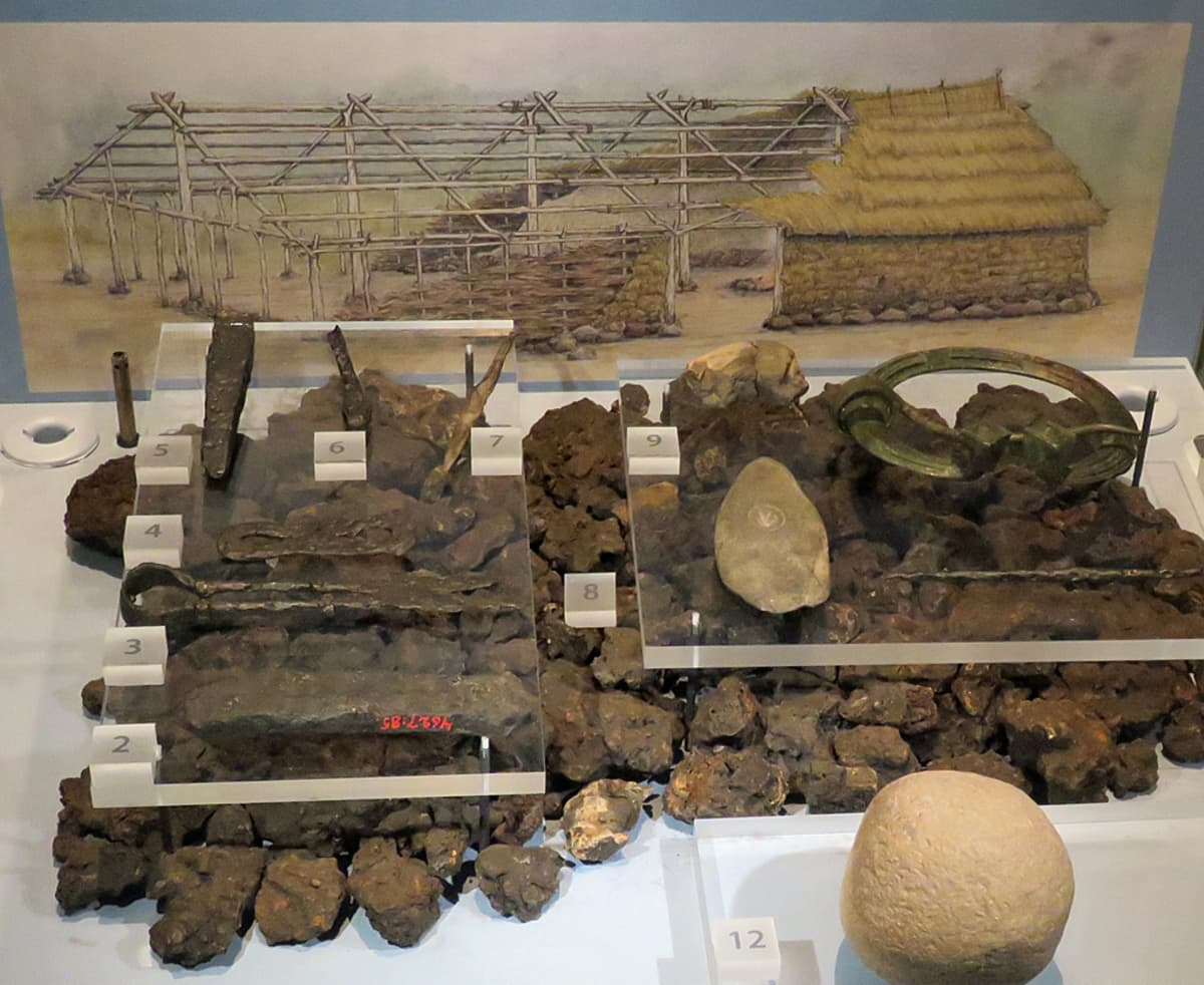 Rakennekuva talosta, jossa on kivistä ladottu jalka, puiset seinä- ja kattopaalut sekä olkikatto. Edessä metallityökaluja ja jauhinkivi.