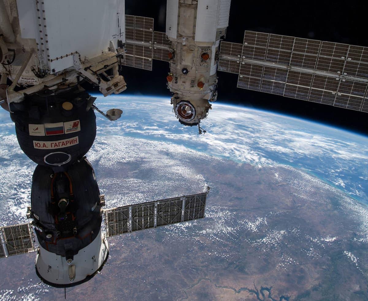 ISS:n moduleja ja osa Sojuz-aluksesta, alla maapallon kaareva pinta pilvien täplittämänä.
