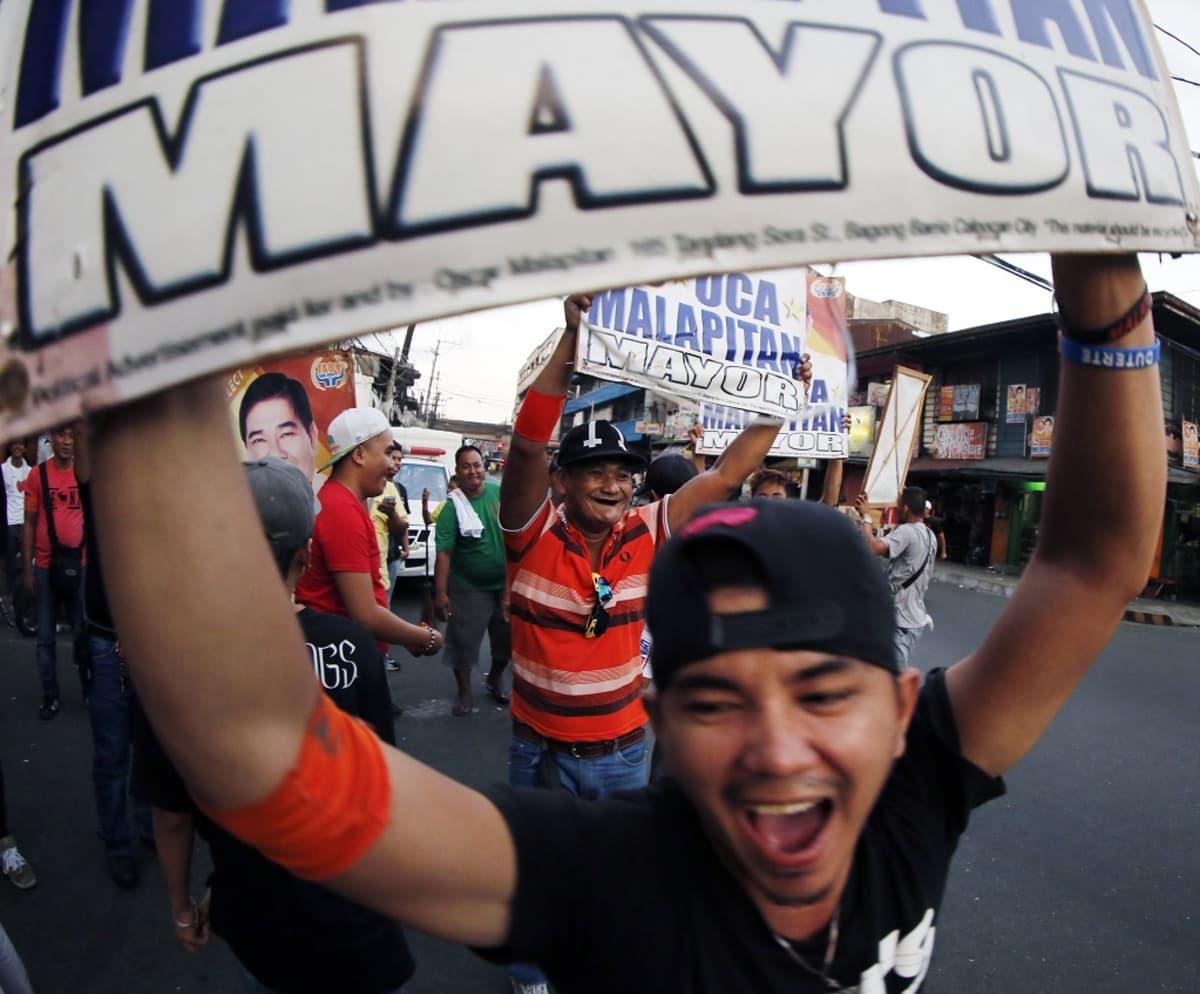 Ihmiset riemuitsevat kadulla Calookanin kaupungissa Manilan pohjoispuolella ensimmäisten vaalitulosten tultua.