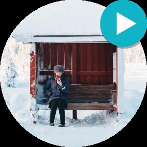 Kuva henkilöstä joka istuu bussipysäkillä talvisessa maisemassa.