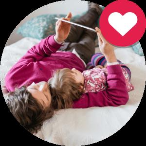 Kuva vanhemmasta ja lapsesta jotka makaavat sängyllä ja katselevat tablettia.