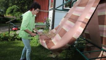 Siivousyrittäjä Aini Lehtosalo tamppaa mattoa.