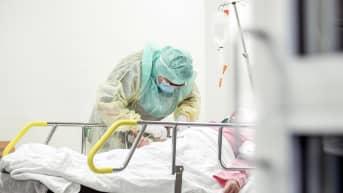 Suojavarustukseen pukeutunut hoitaja ottaa näytettä koronapotilaiden hoitoon tarkoitetulla osastolla Turun yliopistollisessa keskussairaalassa.