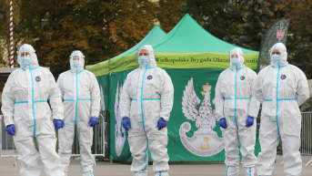 Kuvassa seisoo viisi suojapukuista ihmistä Puolassa.