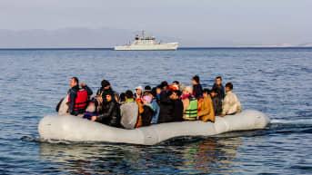 Kuvassa on Frontexin alus ja etualalla pakolaisia.
