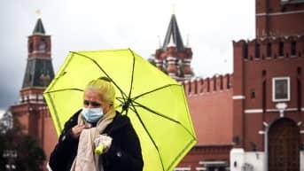 Kasvomaskiin pukeutunut nainen kävelee Kremlin edustalla.