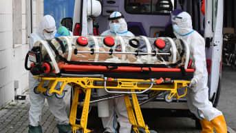 Hoitohenkilökunta siirsi koronaviruspotilasta ambulanssista San Filippo Nerin sairaalaan Roomassa Italiassa 26. lokakuuta.