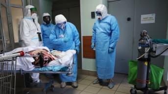 Suoja-asuihin pukeutuneet henkilöt juttelivat potilaalle moskovalaisessa sairaalassa marraskuussa.
