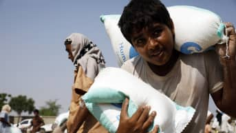 Jemeniläispoika kantaa ruokasäkkejä Hajjahissa Jemenissä syyskuussa 2020.