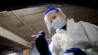 Suojavarusteisiin pukeutunut hoitaja ottaa koronavirustestiä.