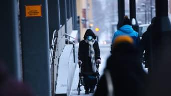 Rollaattorilla kulkeva ihminen kasvomaski kasvoilla Kuopion keskustassa.