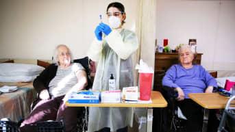 Sairaanhoitaja valmistelee  rokotusannosta vanhusten hoitolaitoksessa.