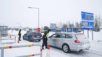 Rajavartijat tarkistavat autoilijoiden henkilöllisyyksiä Tornion ja Haaparannan välisellä rajanylityspaikalla.