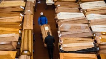 Kaksi miestä kantaa koronaan menehtyneen ruumisarkkua. Ympärillä näkyy kymmeniä koronaan menehtyneiden ruumisarkkuja.