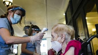 Terveydenhoitohenkilökunta mittaa vanhemman henkilön lämpötilaa.