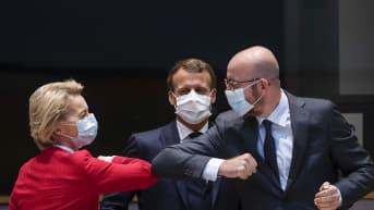Ursula von der Leyen ja Charles Michel kyynärpäätervehtivät ja Emmanuel Macron katsoo taaempana.