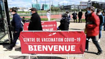 Ihmiset jonottavat rokotuspisteen edustalla.