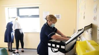 Sairaanhoitaja pakkaa rokotepulloja kylmälaukkuun.
