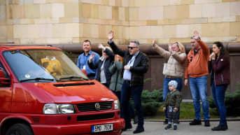 Tšekkiläiset diblomaatit vilkuttavat Moskovan suurlähetystön alueelta autolla poistuville.