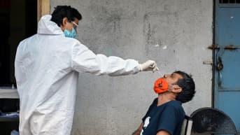 Terveystyöntekijä ottaa koronavirustestiä Mumbaissa.