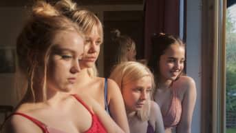 Neljä nuorta katsoo ikkunasta ulos topit tai rintaliivit päällään.