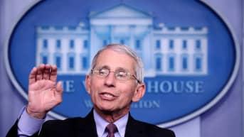 Tohtori Anthony Fauci puhuu ja nostaa oikeaa kättään. Faucilla on tumma puku, vaalea kauluspaita, kravatti ja silmälasit. Taustalla on Valkoisen talon logo.