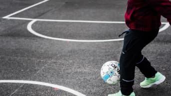 Kuvassa pikkupoika leikkii pallon kanssa.