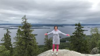 Nainen levittää kätensä ja asettuu valokuvattavaksi Ukko-Kolin huipulla.
