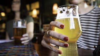 Kaksi henkilö juo olutta ravintolassa.