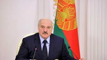 Lukashenka istuu pöydän takana tummassa puvussa ja kravatissa. Seinä on valkoinen, taustalla näky myös