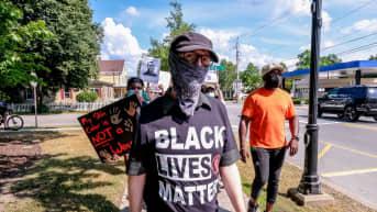 Mies osoittaa mieltä päällään Black Lives Matter -paita.