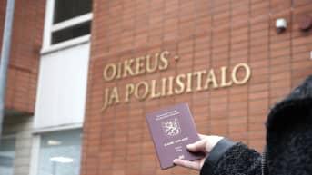 Passi kädessä Kajaanin oikeus- ja poliisitalon edustalla