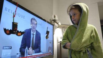 Pikkupoika katsoo televisiota, jossa Belgian pääministeri Alexander De Croo pitää puhetta.