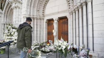 Mies laski kukkia Nizzan Notre-Dame-basilikan edustalle 30. lokakuuta 2020.