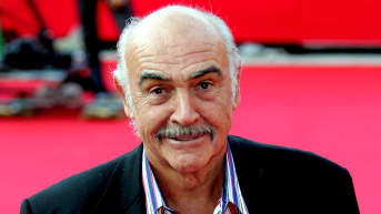 Sean Connery hymyilee punaisella matolla.