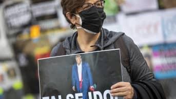 """Nainen kantaa julistetta jossa lukee """"False Idol"""""""
