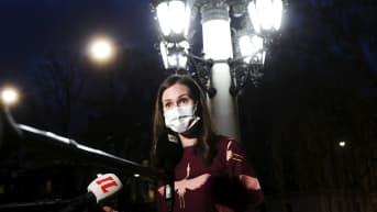 Kvinna i munskydd och vinröd klänning intervjuas framför en lampa. Kvinnan är statsminister Sanna Marin.