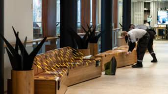 Vartijat teippaamassa yleisiä istumapenkkejä ostoskeskuksessa.