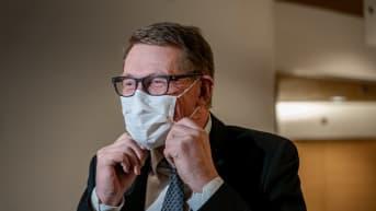 Valtiovarainministeri Matti Vanhanen kohentaa kasvomaskiaan.