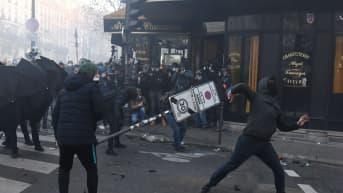 Naamioituneet mielenosoittajat ottavat yhteen poliisin kanssa Pariisissa.