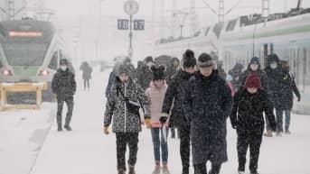 Ihmisiä lumimyräkässä kävelemässä junalaiturilla kohti Rautatientoria.