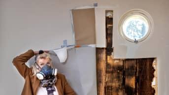 Terttu Aalto kaasunaamari naamallaan, esittelee talonsa sisätiloissa esiintyvää kreosoottia.