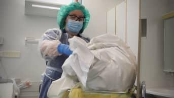 Laitoshuoltaja pakkaa eristyspyykkiä sairaalassa.