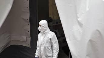 Valkoiseen suojaasuun, maskiin ja sinisiin käsineisiin pukeutunut työntekijä seisoo suuren valkoisen telttamaisen oviaukon suulla.