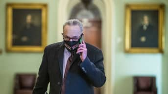 Kasvomaskiin pukeutunut Chuck Schumer puhuu puhelimeen kongressin käytävällä