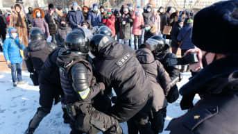 mellakkavarusteisiin pukeutuneet poliisit pidättävät mielenosoittajaa lumisessa kaupungissa
