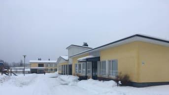 Ilomantsin peruskoulun keltaisia rakennuksia talvella.