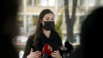 Svartklädd kvinna i svart munskydd talar utomhus med många mikrofoner framför sig. Statsminister Sanna Marin (SDP) kommenterar träffen med riksdagsgrupperna den 25 februari 2021.
