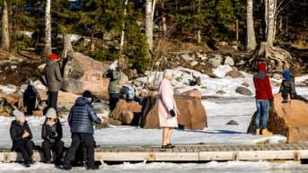 Ihmisiä nauttimassa aurinkoisesta säästä talvimaisemassa.