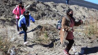 Äiti ja kaksi tytärtä juoksevat Yhdysvaltain ja Meksikon rajajoella.
